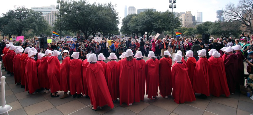 """Women dressed in """"Handmaids Tale"""" costumes stand on the steps of the state Capitol at the start of a rally for reproductive rights."""