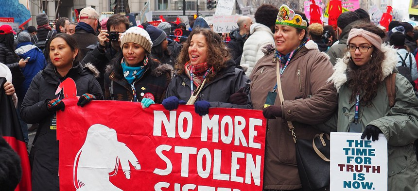 Protestors at the 2019 Women's March in Washington, D.C. hold up a poster highlighting the Missing and Murdered Indigenous Women crisis (MMIW).