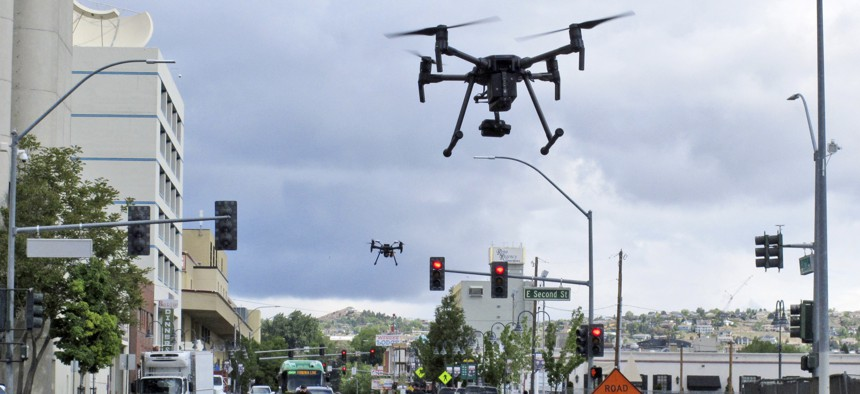 In this May 21, 2019 photo, two drones fly above Lake Street in downtown Reno, Nev., as part of a NASA simulation to test emerging technology.