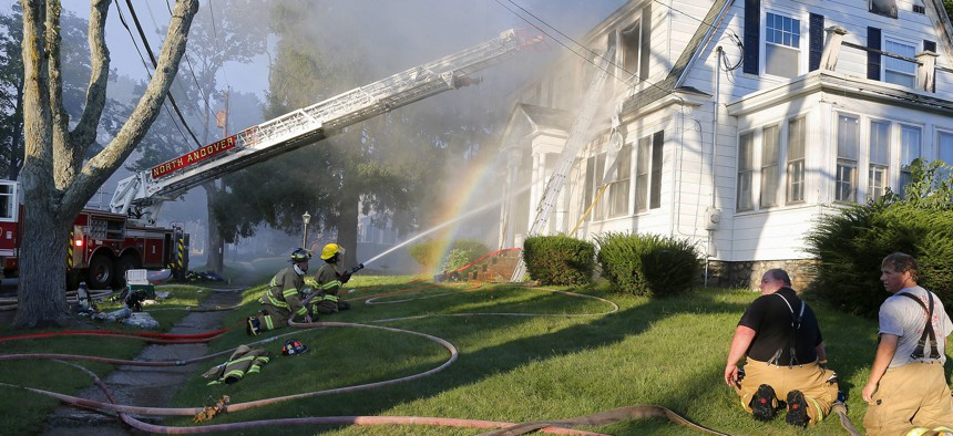 Firefighters battle a house fire, Thursday, Sept. 13, 2018, in North Andover, Mass., one of multiple emergency crews responding to a series of gas explosions and fires triggered by a problem with a gas line that feeds homes in several communities.