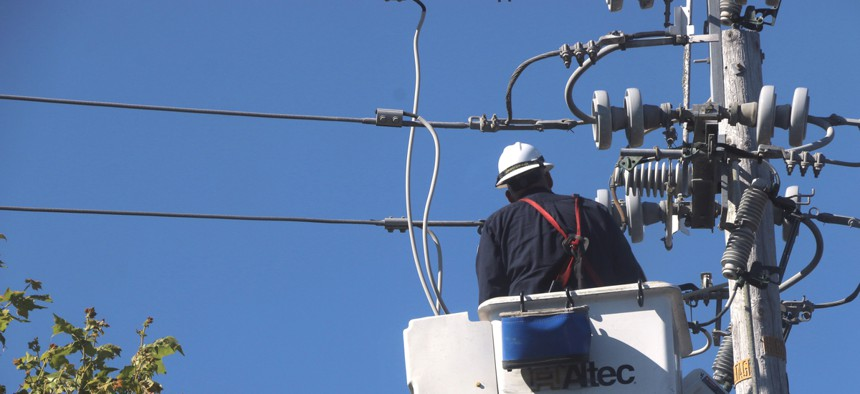 A PG&E employee inspects a power line after an outage.