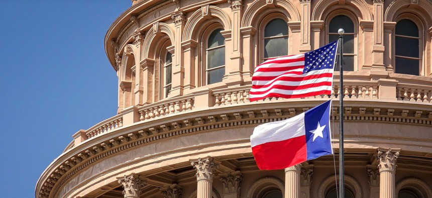 American and Texas state flags flying on the dome of the Texas State Capitol building in Austin.