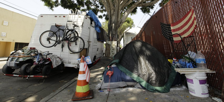 A RV vehicle is parked next to a tent on the streets in an industrial area of Los Angeles, Wednesday, July 31, 2019.