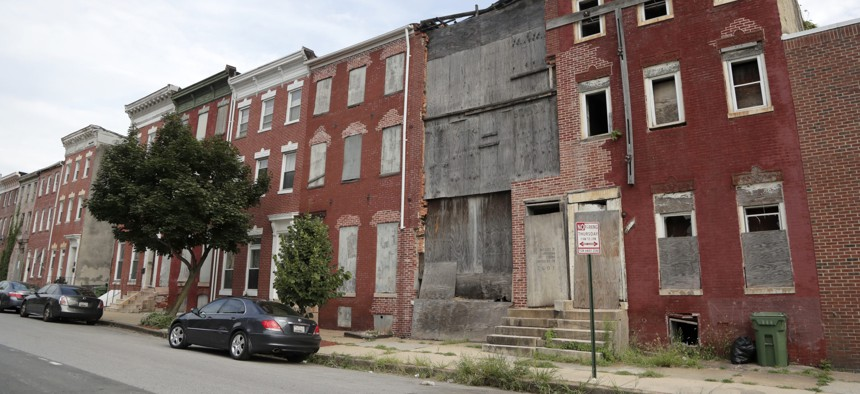 Boards cover the front end of a abandoned row homes in the vicinity of an opportunity zone in Baltimore.