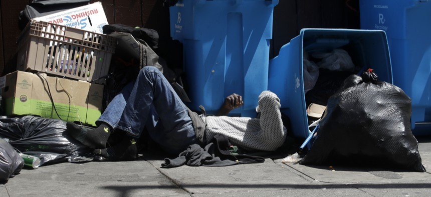 A homeless man sleeps in front of recycling bins and garbage on a street corner in San Francisco on Aug. 21, 2019.