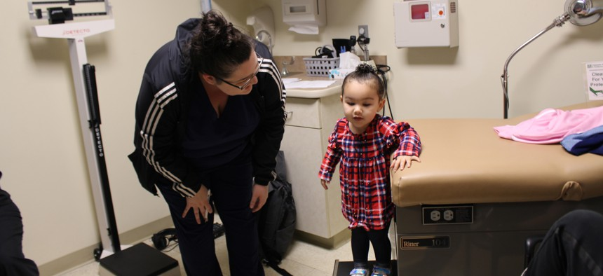 Eliza Oliver helps her daughter, Taelyn, step down from the exam table after her wellness check at Community Health Center.