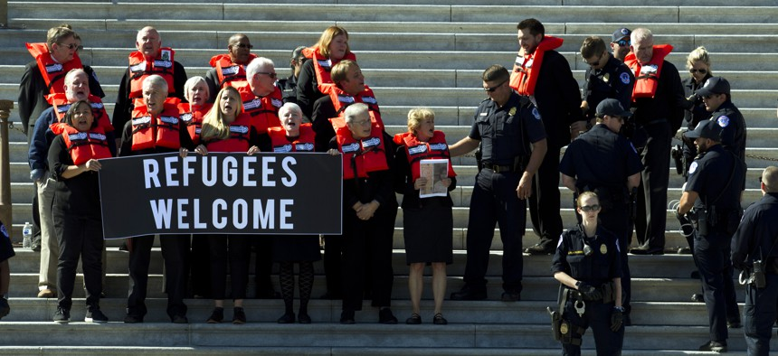 In this Oct. 15, 2019 file photo, faith leaders and members of human rights groups wearing a life vests symbolizing the life-saving program are arrested during a protest calling congress not to end refugee resettlement program.