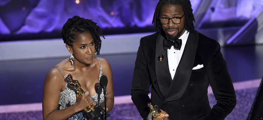 """Karen Rupert Toliver, left, and Matthew A. Cherry accept the award for best animated short film for """"Hair Love"""" at the Oscars."""