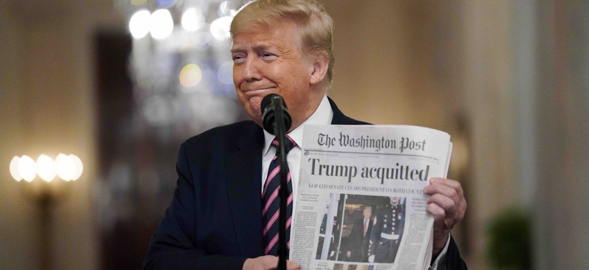 """President Donald Trump holds a copy of The Washington Post as he speaks in the East Room of the White House, Thursday, Feb. 6, 2020, in Washington. Trump has described the news outlet and others as """"fake news"""" during the course of his presidency."""