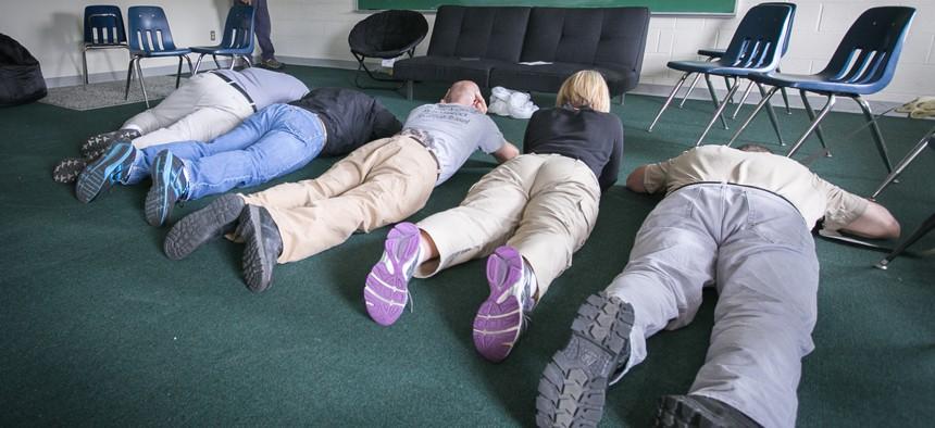 School employees play dead on the floor during an active shooter mock scenario in Rittman, Ohio, in June 2014.