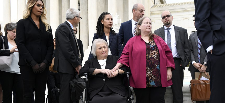 Aimee Stephens, seated center, listens during a news conference outside the Supreme Court. Stephens' case about her firing from a funeral home after her transition will determine transgender people's employment protections.