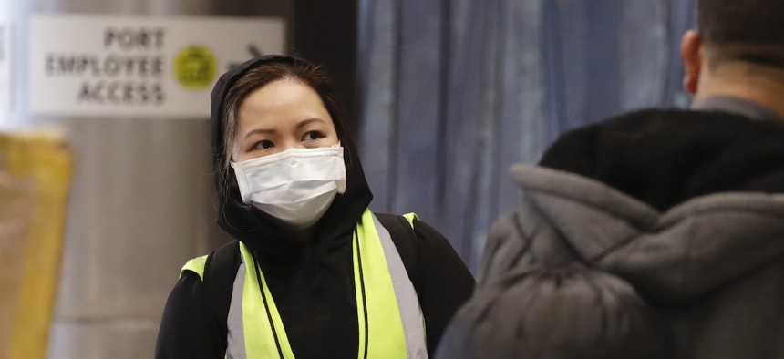 An airport agent wears a protective mask as she waits to assist international travelers at SeaTac International Airport on Monday.