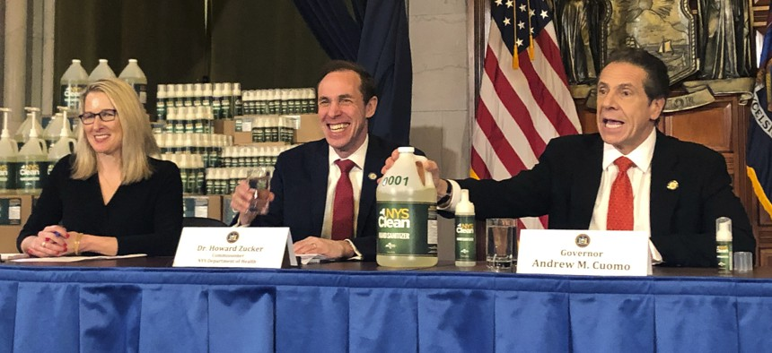 """New York Gov. Andrew Cuomo, right, introduces """"New York State Clean,"""" a hand sanitizer manufactured by the state on March 9, 2020 in response to the coronavirus."""