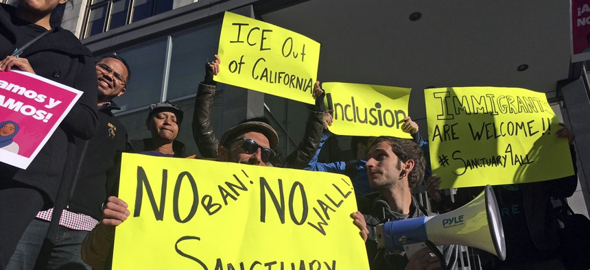 Protesters stand outside a courthouse in San Francisco during a hearing for a lawsuit challenging President Trump's 2017 executive order to withhold funding from communities that limit cooperation with immigration authorities.