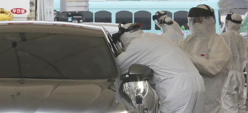 Medical staff in a South Korean drive-thru testing center swab a patient for Covid-19.