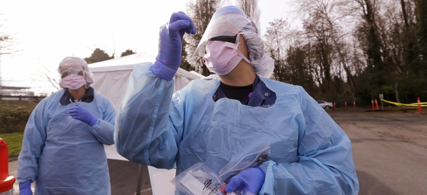 Theresa Malijan, a registered nurse, holds up her hand as she demonstrates how she collects a swab from patients at a drive-through COVID-19 and caronavirus testing station for University of Washington Medicine patients, March 17, 2020, in Seattle.