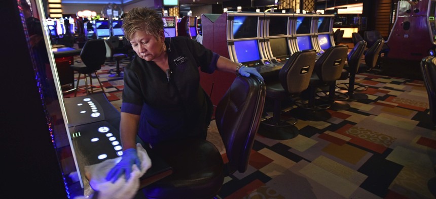 Antonia Garcia cleans slot machines inside the Planet Hollywood hotel-casino after all casinos in the state were ordered to shut down due to the coronavirus Wednesday, March 18, 2020, in Las Vegas.