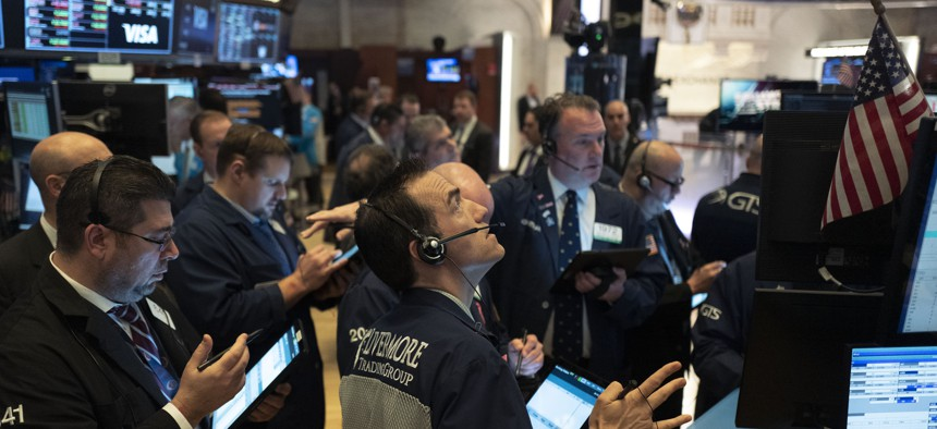 Traders work at the New York Stock Exchange, Wednesday, March 18, 2020 in New York. Global stock markets have sunk in a third day of wild price swings after President Donald Trump promised to prop up the U.S. economy through the coronavirus outbreak.
