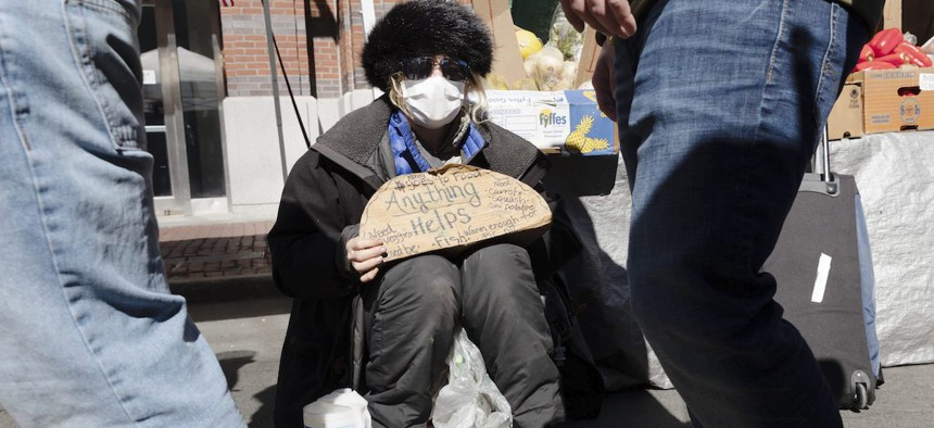 A homeless woman going by the name of Miss Bee seeks donations at an outdoor produce market in Boston, Saturday, March, 14, 2020.