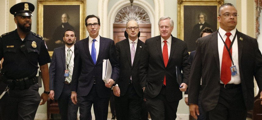Treasury Secretary Steven Mnuchin, left, accompanied by White House Legislative Affairs Director Eric Ueland and acting White House chief of staff Mark Meadows, walks to the offices of Senate Majority Leader Mitch McConnell on Capitol Hill in Washington.