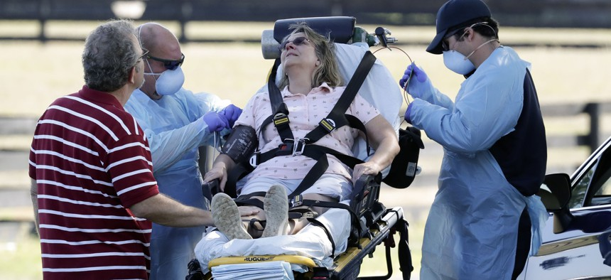 Medical personnel treat a woman shortly after she arrived at a coronavirus mobile testing site Monday, March 23, 2020, in The Villages, Fla. She was later transported to a medical facility by ambulance.