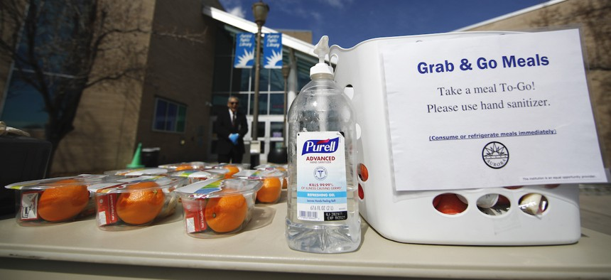 A bottle of hand sanitizer stands next to free lunches for people under the age of 18 outside the Aurora Public Library on Wednesday, March 25.