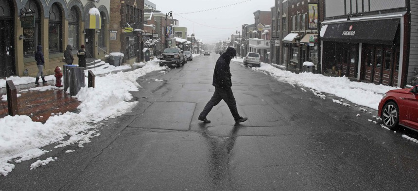 A man walks across Main Street Thursday, March 26, 2020, in Park City, Utah. After seeing a surge of coronavirus cases, Summit County issued an order for all residents to not leave their homes unless necessary.