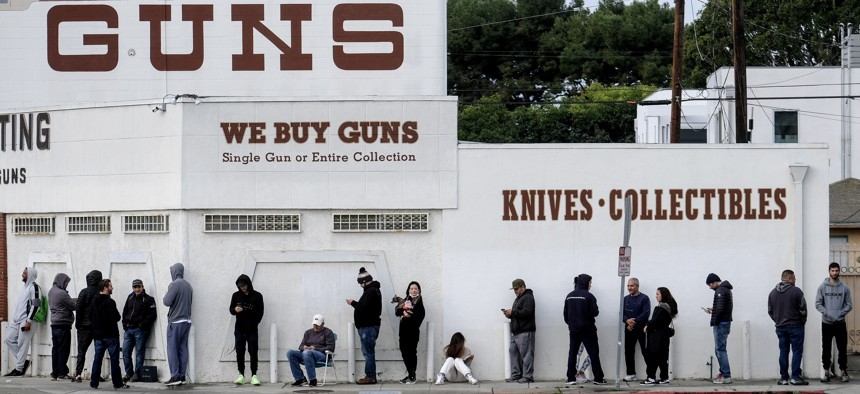 People wait in a line to enter a gun store in Culver City, Calif., Sunday, March 15, 2020. Coronavirus concerns have led to consumer panic buying of grocery staples, and now gun stores are seeing a similar run on weapons.