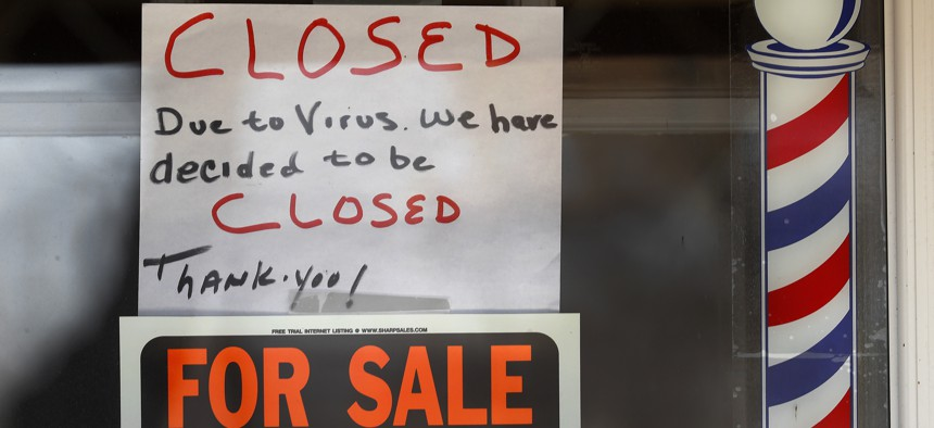 """""""For Sale By Owner"""" and """"Closed Due to Virus"""" signs are displayed in the window of Images On Mack in Grosse Pointe Woods, Mich., Thursday, April 2, 2020."""