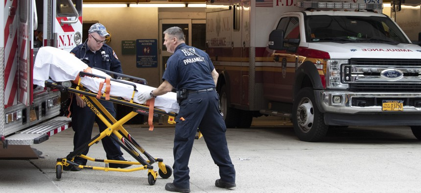 FDNY paramedics place an empty collapsible wheeled stretcher into an ambulance after delivering a patient into the emergency room at NewYork-Presbyterian Lower Manhattan Hospital, Wednesday, March 18, 2020, in New York.