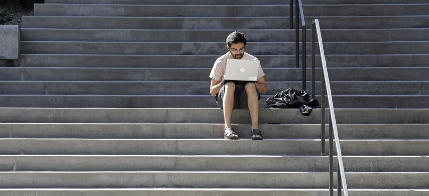 Amazon software engineer Aditya Iyer sits alone on steps outside the company headquarters as he works on his laptop Friday, March 20, 2020.