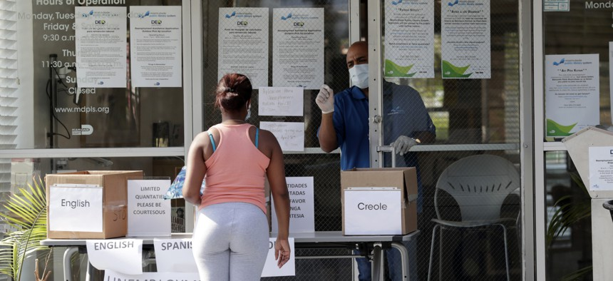 In this April 8, 2020 photo, Harry Varela, right, wears a protective mask as he talks with a woman requesting an unemployment form at a Miami-Dade County library during the new coronavirus pandemic in Miami.