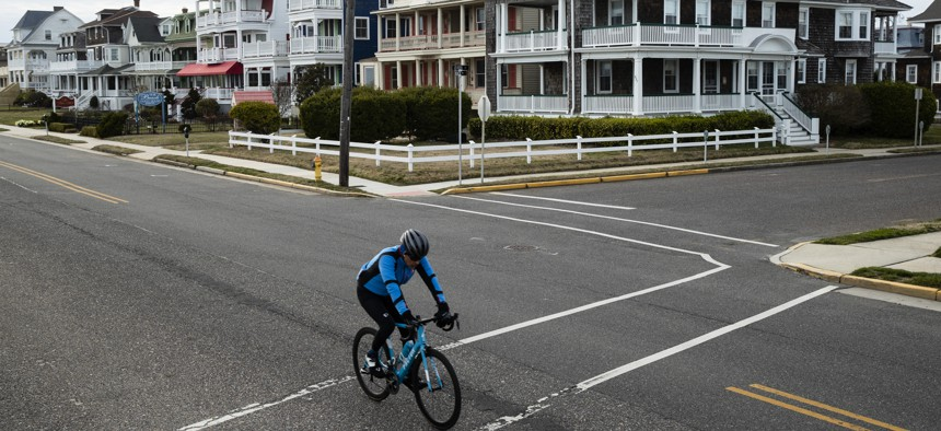 A cyclist rides a bicyle in Cape May, N.J., Wednesday, March 18, 2020.Some people who live in cities or their suburbs have been fleeing to their second homes at the shore to ride out the coronavirus near the beach.