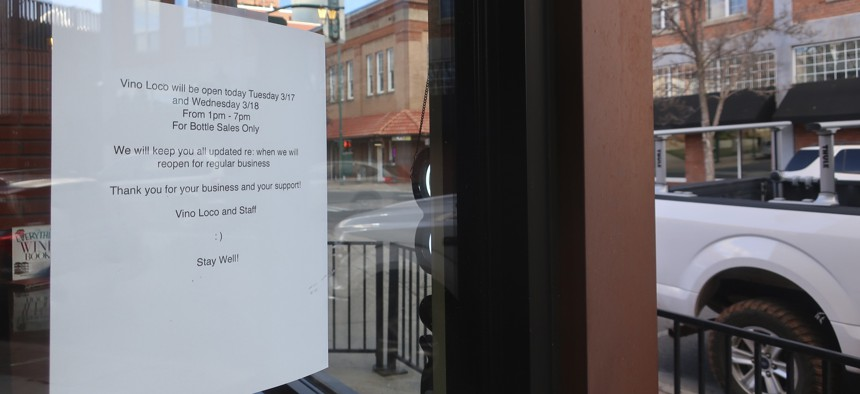 A sign at a wine shop in downtown Flagstaff, Ariz., Tuesday, March 17, 2020, lets customers know the shop will be closed temporarily. The mayor of Flagstaff ordered restrictions on restaurants and the closure of other businesses due to the coronavirus.