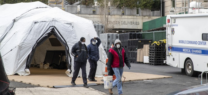 Medical Examiner personnel and construction workers are seen at the site of a makeshift morgue being built in New York City on March 25, 2020.
