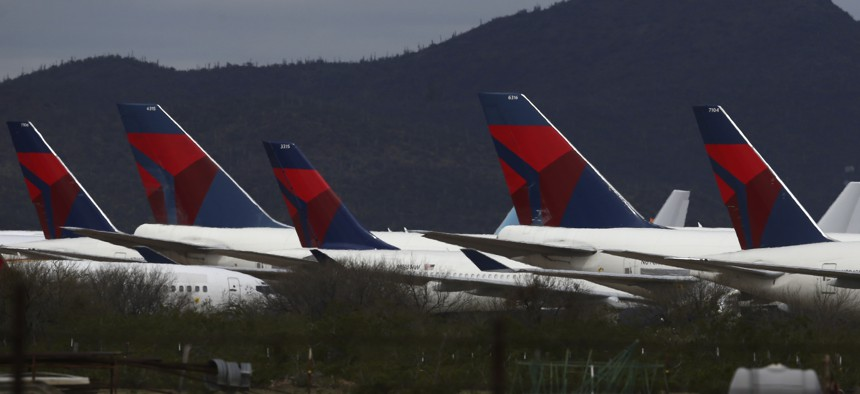 Tail fins of recently landed Delta Air Lines sit parked at Pinal Airpark on March 18, 2020, in Red Rock, Ariz.