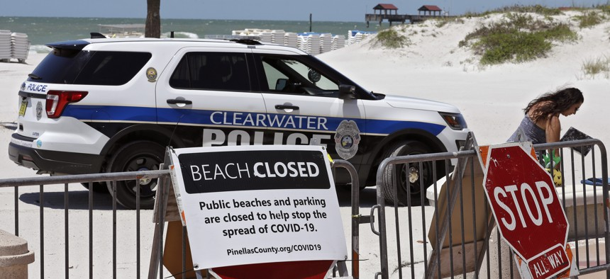 A Clearwater police officer asks a woman who was sitting on Clearwater Beach to leave Thursday, April 30, 2020, in Clearwater Beach, Fla. The beach is temporarily closed to avoid the spread of the coronavirus.