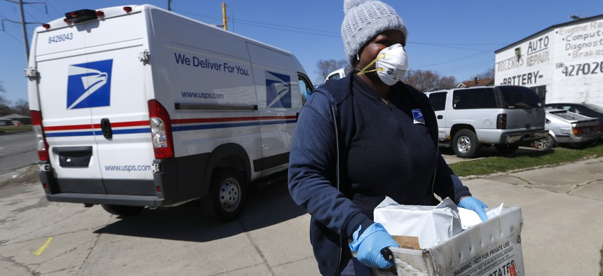 A United States Postal worker makes a delivery with gloves and a mask in Warren, Mich. on April 2, 2020.