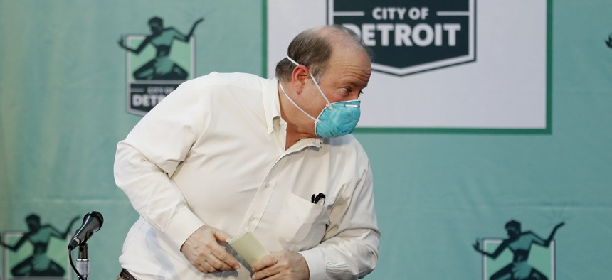 Detroit Mayor Mike Duggan exits a news briefing in April after announcing layoffs, pay cuts for other employees and and a reduction in some services. On Monday, he said up to 200 workers would soon return to their normal duties.