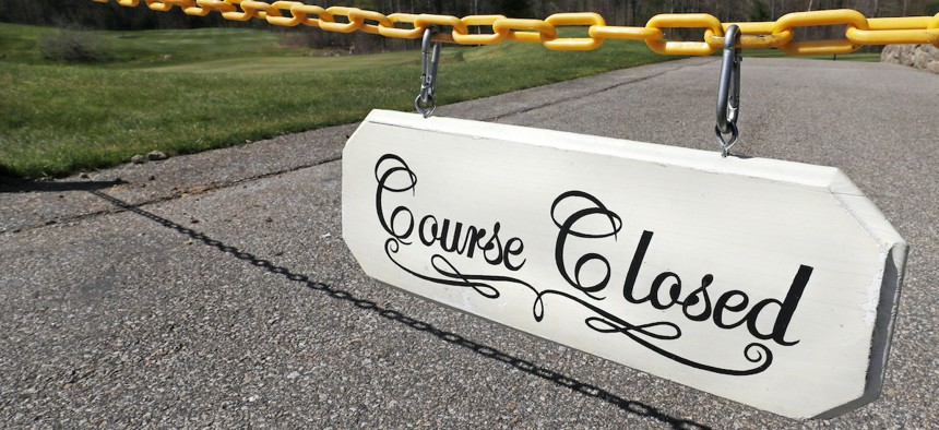 """A """"Course Closed"""" sign blocks a cart path leading to the first tee box at the Brookstone Park Golf Complex in Derry, N.H., Tuesday, May 5, 2020. Golf courses reopened to members and state residents Monday."""