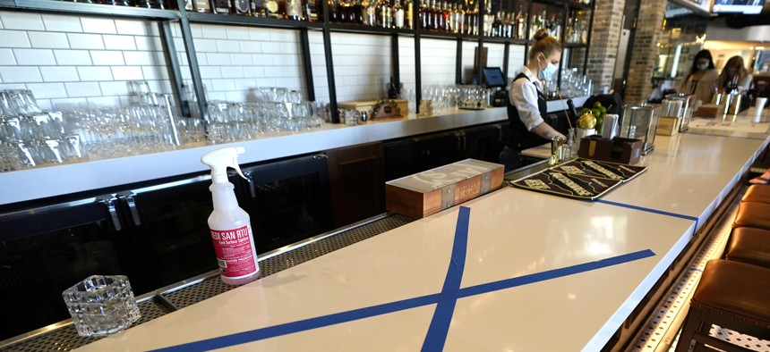 A bottle of sanitizer sits on the bar as tape marks an area to keep clear for social distancing at a Houston restaurant on April 24, 2020.