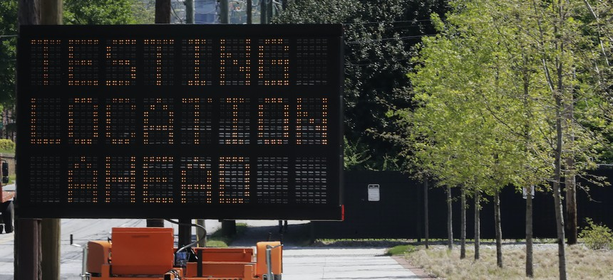 """A sign reading """"Testing Location Ahead"""" is seen near the COVID-19 testing area on Georgia Tech's campus, Monday, April 6, 2020, in Atlanta."""