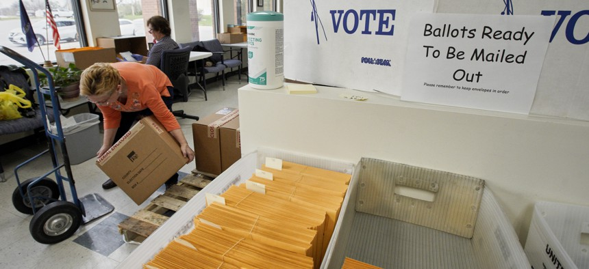In this April 14, 2020 photo, Nadette Cheney picks up a box of printed ballots as others work on preparing mail-in ballots at the Lancaster County Election Committee offices in Lincoln, Neb.