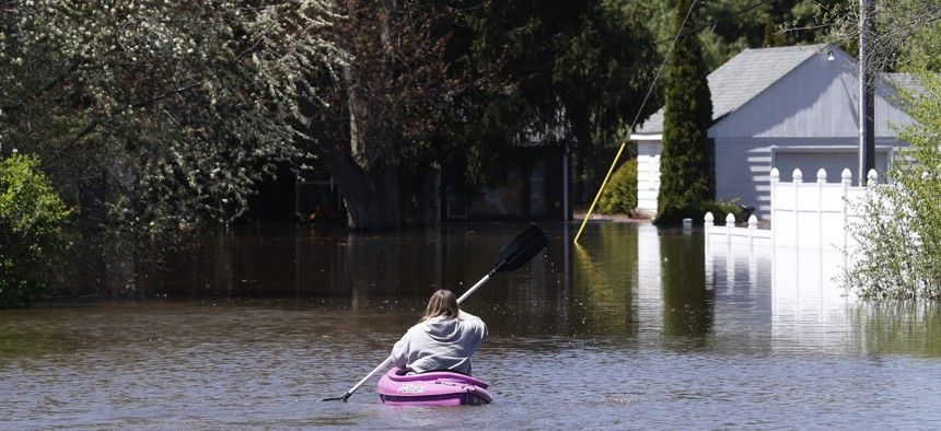 A kayaker paddles out to check on a residence as the Tittabawassee River overflows, Wednesday, May 20, 2020, in Midland, Mich.