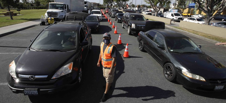 Cars line up at a food distribution center Friday, May 15, 2020, in Compton, Calif.