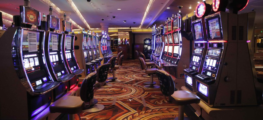 Chairs have been removed at some electronic slot machines to maintain social distancing between players at a closed Caesars Palace hotel and casino Thursday, May 21, 2020, in Las Vegas. Casinos are awaiting to reopen amid the coronavirus outbreak.