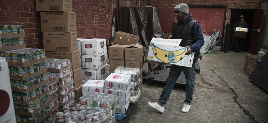 A volunteer at the St. Stephen Outreach carries food donations as he prepares to hand out food in the Brooklyn borough of New York on March 20, 2020.