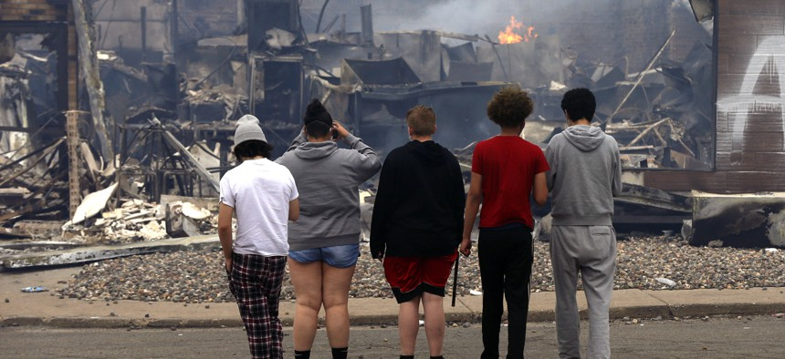 Onlookers watch as smoke smolders from a destroyed fast food restaurant near the Minneapolis Police Third Precinct on May 28, 2020, after a night of looting as protests continue over the death of George Floyd, who died in police custody on Monday.