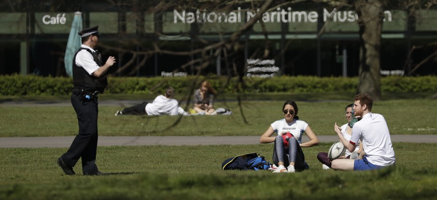 As England began to implement coronavirus restrictions in early April, a police officer asks people who were sitting down on the grass to move on in Greenwich Park, London.