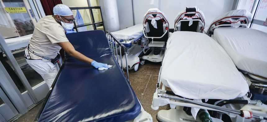 A medical worker wearing personal protective equipment cleans gurneys in the emergency department intake area at NYC Health + Hospitals Metropolitan, Wednesday, May 27, 2020, in New York. (AP Photo/John Minchillo)